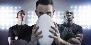 Złożony wizerunek twarda rugby gracza mienia piłka Obrazy Royalty Free