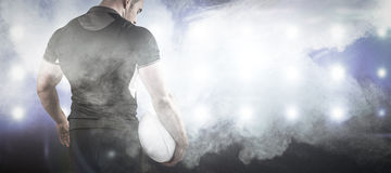 Złożony wizerunek twarda rugby gracza mienia piłka Obraz Stock