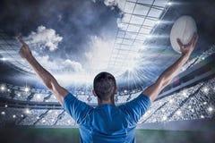 Złożony wizerunek tylni widok rugby gracza mienia piłka z rękami podnosić Fotografia Stock