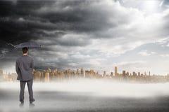 Złożony wizerunek tylni widok z klasą biznesmena mienia popielaty parasol Obraz Stock