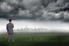 Złożony wizerunek tylni widok z klasą biznesmena mienia popielaty parasol Fotografia Stock