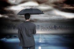 Złożony wizerunek tylni widok z klasą biznesmena mienia popielaty parasol Obrazy Royalty Free