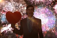 Złożony wizerunek uśmiecha się serce kartę i trzyma geeky biznesmen Fotografia Stock