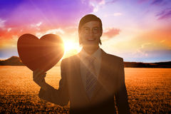 Złożony wizerunek uśmiecha się serce kartę i trzyma geeky biznesmen Obrazy Royalty Free