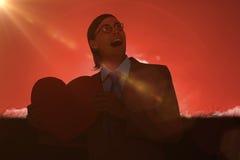 Złożony wizerunek uśmiecha się serce kartę i trzyma geeky biznesmen Obraz Royalty Free