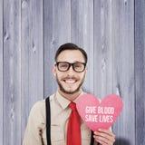 Złożony wizerunek uśmiecha się serce kartę i trzyma geeky modniś Obrazy Stock
