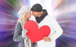 Złożony wizerunek uśmiechnięta para w zimy modzie pozuje z kierowym kształtem Fotografia Stock