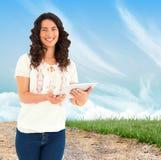 Złożony wizerunek uśmiechnięta przypadkowa brunetka używać jej pastylka komputer osobistego Fotografia Stock