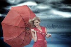Złożony wizerunek uśmiechnięty blondynki mienia parasol fotografia stock