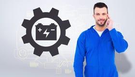 Złożony wizerunek uśmiechnięty męski mechanik używa jego telefon komórkowego Obrazy Stock