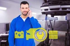 Złożony wizerunek uśmiechnięty męski mechanik używa jego telefon komórkowego Obraz Royalty Free