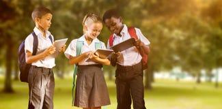 Złożony wizerunek ucznie w mundurach używać cyfrowe pastylki zdjęcie royalty free