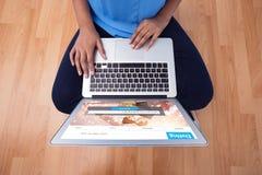 Złożony wizerunek w połowie sekcja żeński wykonawczy używa laptop podczas gdy siedzący na drewnianej podłodze fotografia stock