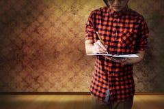 Złożony wizerunek w połowie sekcja młodego człowieka writing na notatniku obraz royalty free