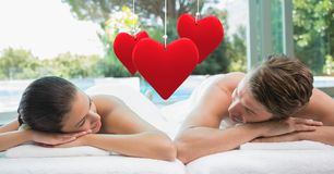 Złożony wizerunek wiszący czerwony serca i pary lying on the beach przy zdrojem Zdjęcie Stock