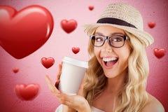 Złożony wizerunek wspaniały uśmiechnięty blondynka modniś przedstawia oddaloną filiżankę Zdjęcia Stock