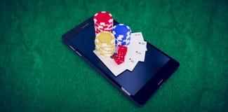 Złożony wizerunek wysokiego kąta widok telefon komórkowy z kasynowymi żetonami i karta do gry Obrazy Stock