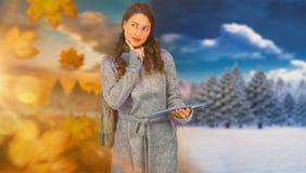 Złożony wizerunek zadumany wzorcowy jest ubranym zimy odzieżowy mienie jej pastylka Fotografia Stock