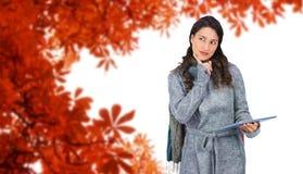 Złożony wizerunek zadumany wzorcowy jest ubranym zimy odzieżowy mienie jej pastylka Obraz Stock