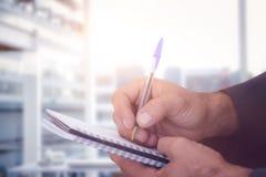 Złożony wizerunek zakończenie up mężczyzna writing w spirali książce Fotografia Stock