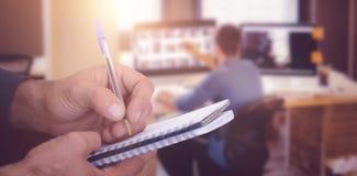 Złożony wizerunek zakończenie up mężczyzna writing w spirali książce Zdjęcie Royalty Free