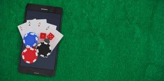 Złożony wizerunek zasięrzutny widok telefon komórkowy z kasynowymi żetonami i karta do gry Obrazy Stock