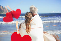 Złożony wizerunek zawijający up w koc na plażowy przyglądającym out morze para Fotografia Royalty Free