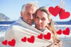 Złożony wizerunek zawijający up w koc na plaży uśmiechnięta para Obraz Stock