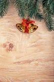 Złociści Bożenarodzeniowi dzwony i jedlinowa gałąź na nieociosanym drewnianym tle karciany ilustraci wektoru xmas szczęśliwego no Zdjęcia Stock