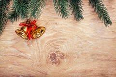 Złociści Bożenarodzeniowi dzwony i jedlinowa gałąź na nieociosanym drewnianym tle karciany ilustraci wektoru xmas szczęśliwego no Obrazy Stock