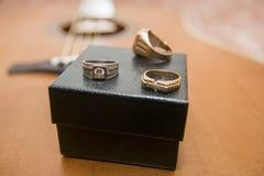 Złociści pierścionki, skrzynka i gitara akustyczna w tle, Zdjęcia Stock