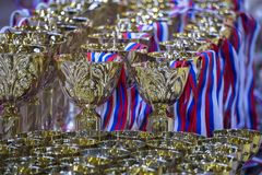 Złociści trofea z purpurowym białym i błękitnym faborkiem dla rywalizaci Złocista filiżanka dla nagrody wygrania Zdjęcia Royalty Free