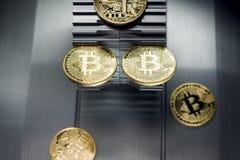 Złoci bitcoins kłamają na metalu gearwheel obraz stock