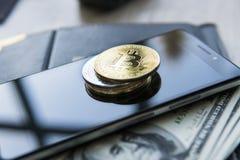 Złoci bitcoins na mądrze nas i telefonie dolary z notatnikiem na tle Bitcoin crypto currebcy Cyfrowej waluta obrazy stock