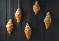 Złoci croissants na nieociosanym czarnym drewnianym tle zdjęcie stock