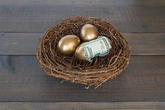 Złoci jajka w gniazdeczku z jeden jajkiem pękającym otwierają z pieniądze Obraz Stock
