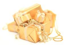 Złoci prezentów pudełka z złotym faborkiem na białym tle Obrazy Royalty Free