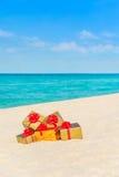 Złoci zawijający galanteryjni pudełka z łękami przy tropikalnym oceanem wyrzucać na brzeg Obraz Stock