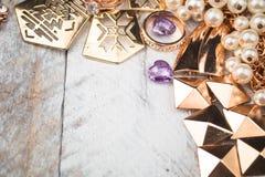 Złocista biżuteria dla eleganckich kobiet na białym drewnianym tle Obraz Stock
