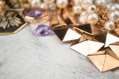 Złocista biżuteria dla eleganckich kobiet na białym drewnianym tle Fotografia Stock