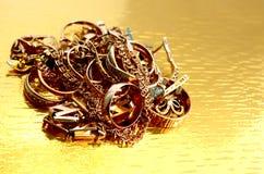 Złocista biżuteria, składający stos na złocistym tle Obraz Royalty Free