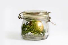 Złocista Bożenarodzeniowa piłki i świerczyny gałąź w szklanym słoju Odizolowywający na bielu fotografia stock