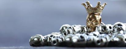 Złocista czaszka wśród zwyczajnych metal czaszek Fotografia Stock