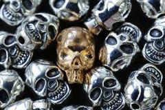 Złocista czaszka wśród zwyczajnych metal czaszek Zdjęcia Royalty Free