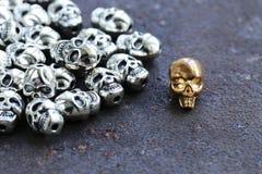 Złocista czaszka wśród zwyczajnych metal czaszek Fotografia Royalty Free