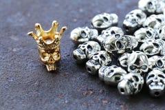 Złocista czaszka wśród zwyczajnych metal czaszek Zdjęcie Stock