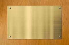 Złocista lub mosiężna metal plakieta na drewnianym tle fotografia royalty free