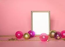 Złocista obrazek rama z boże narodzenie ornamentami Mockup na różowym tle Mody dekoracja Zdjęcia Stock