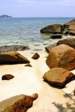 Złocista piasek plaża z kamiennymi skałami Obraz Stock