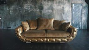 Złocista rzemienna kanapa w loft na tle zbiory
